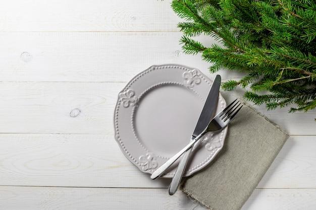 クリスマスまたは新年の背景、モミの木、プレート、カトラリー、ホワイトボード