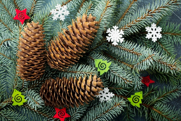 Рождество или новый год. большая ветка фит-дерева с шишками, деревянными игрушками и снежинками.