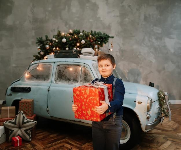 幸せな男の子とスタジオで飾られたレトロな青い車とクリスマスまたは年賀状