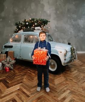 Рождественская или новогодняя открытка со счастливым мальчиком и украшенной синей ретро-машиной в студии