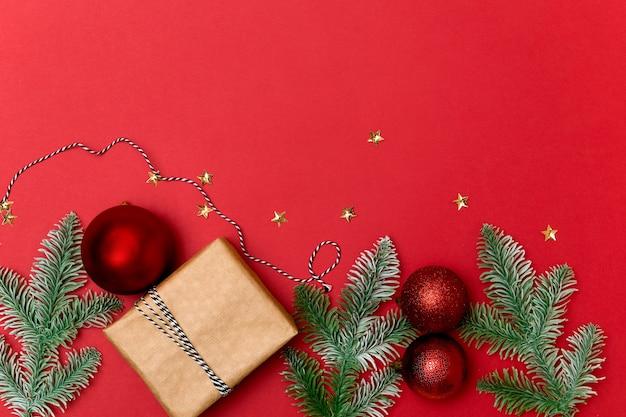 크리스마스 또는 새 해 색상 평면 선물 상자 전나무 나무 가지와 공 빨간색 배경 복사 공간 누워