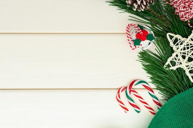 白い木製の背景にクリスマスや新年の構成。松の枝、ジングルベル、キャンディケイン
