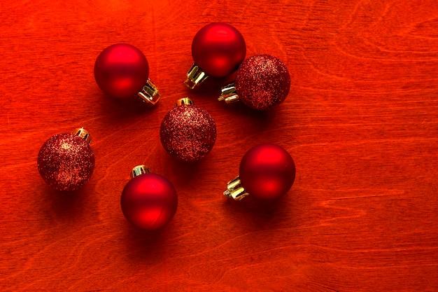 クリスマスまたは新年の作曲。コピースペースと赤い木製の背景に赤いクリスマスボール。