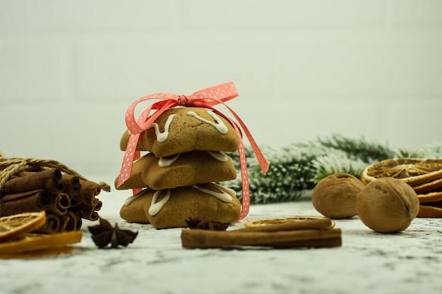축제 장식, 겨울 향신료, 크리스마스 장식, 견과류와 전나무 가지, 진저브레드 쿠키가 있는 크리스마스 또는 새해 구성