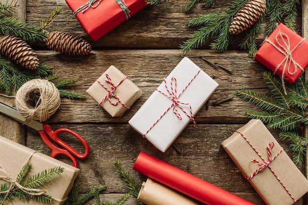 ギフトボックス、モミの枝、木の背景に赤いボールとクリスマスや新年の構成。