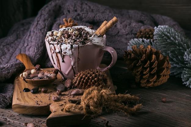 素朴な木の板に刻んだチョコレートとカカオ豆を添えたホイップクリームとホットチョコレートまたはココアドリンクを使ったクリスマスまたは新年の組成物。