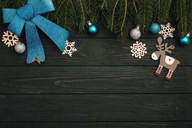 クリスマスまたは新年の暗い木製の背景、季節の装飾で囲まれたクリスマスの黒板、上からの眺め