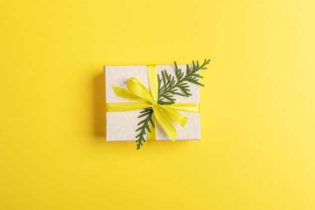Подарочная коробка своими руками на рождество или новый год, украшенная желтой лентой с бантом и зеленой веткой туи в центре ярко-желтого фона. рождественский фон, украшения. вид сверху. скопируйте место для текста.