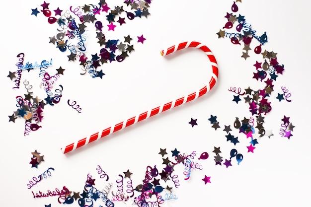 クリスマスや新年のお祭りの背景。縞模様のキャンディーとカラフルなキラキラのグリーティングカードの構成。休日の概念。