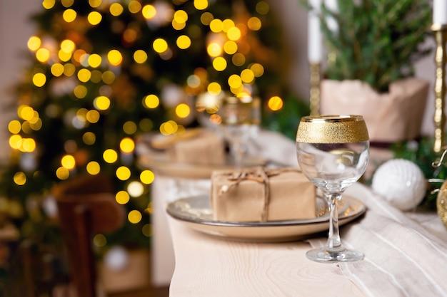 Рождественский или новогодний праздничный стол, сервировка бокала шампанского на столе