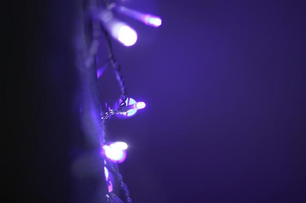 カラフルな花輪のライトでクリスマスや新年のお祝いのぼやけた背景