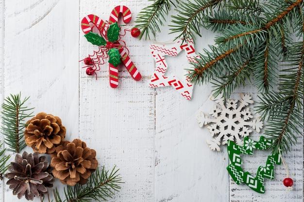 クリスマスまたは新年。モミの木の枝、クリスマスツリーのおもちゃ、星、スノーフレーク、白い木の上の円錐形。