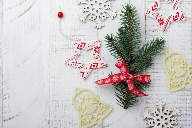 Рождество или новый год. елочные ветви, елочные игрушки, звезды, снежинки и шишки на белом деревянном.