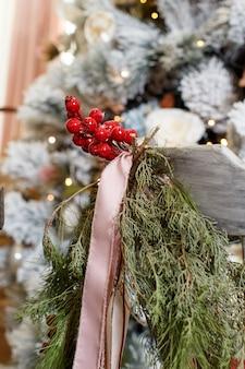 Рождественский или новогодний домашний декор на стуле, лентах, ягодах и ветвях, рождественской елке на фоне. деталь празднования зимнего праздника
