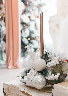 Рождественский или новогодний домашний декор со свечными еловыми ветками и шарами на деревянной лестнице