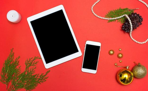クリスマスまたは新年のipadのiphoneのタブレットスマートフォンのモバイルアプリケーションの背景:モミの木の枝、金のガラスのボール、装飾とコーン
