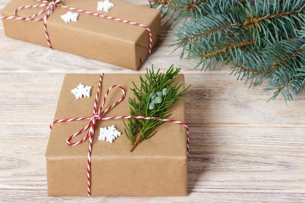 크리스마스 또는 새해 선물은 천연 색종이로 싸여 있고 흰색 배경에 전통적인 크리스마스 꼬기와 전나무 나뭇가지로 장식되어 있습니다.