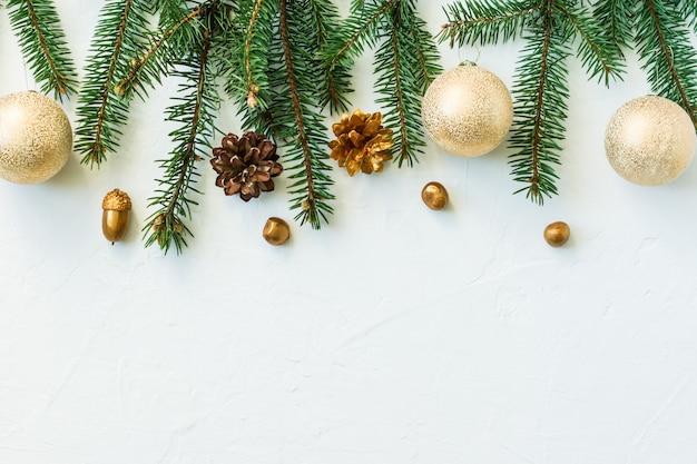 나뭇가지와 가문비나무 콘, 황금색 공, 견과류가 있는 크리스마스 또는 새해 배경. 평면도. 공간의 사본.