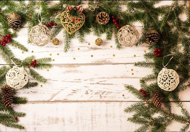 가문비나무, 원뿔, 금색 장난감, 투각 공의 녹색 가지가 있는 크리스마스 또는 새해 배경. 텍스트를 위한 공간의 복사본입니다.