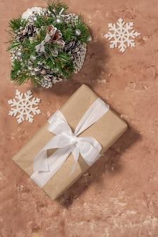 クリスマスまたは新年の作曲。ベージュのテクスチャ背景にコーンと雪片で作られた装飾的なクリスマスツリーの近くに白いリボンが付いたクリスマスギフトボックス。フラットレイ、上面図。