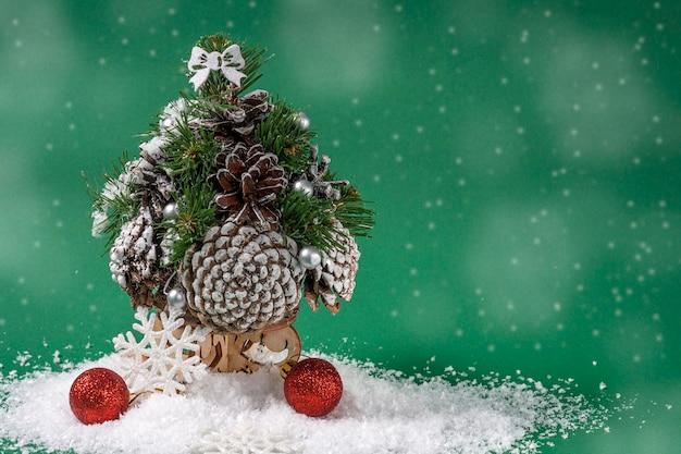 クリスマスまたは新年の作曲。雪片とボケ味の緑の背景に雪の上の円錐形と赤いボールで作られた装飾的なクリスマスツリー。