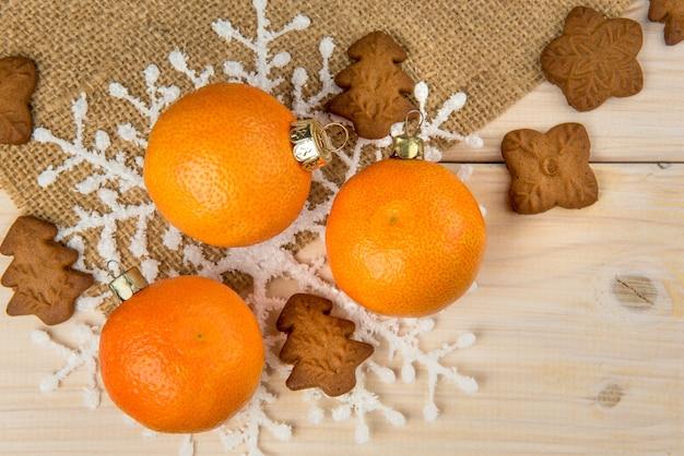 Рождественские или новогодние мандарины и имбирные пряники со снежинками, обрамленные на деревянном фоне с фоном коричневого мешка