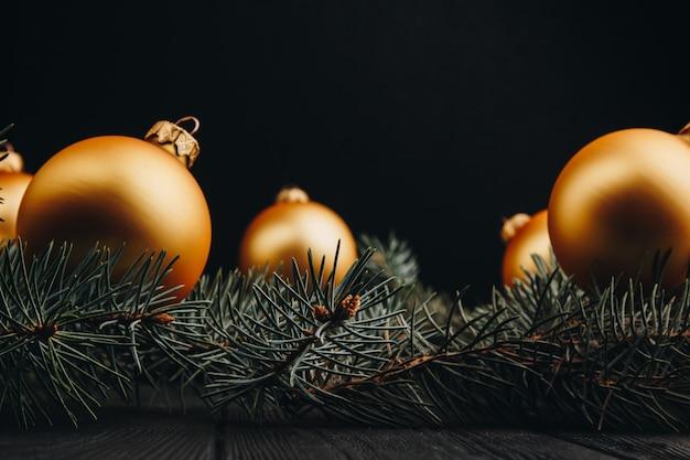 Рождественские или новогодние елочные игрушки золотые шарики и ветка ели деревенские на деревянном фоне