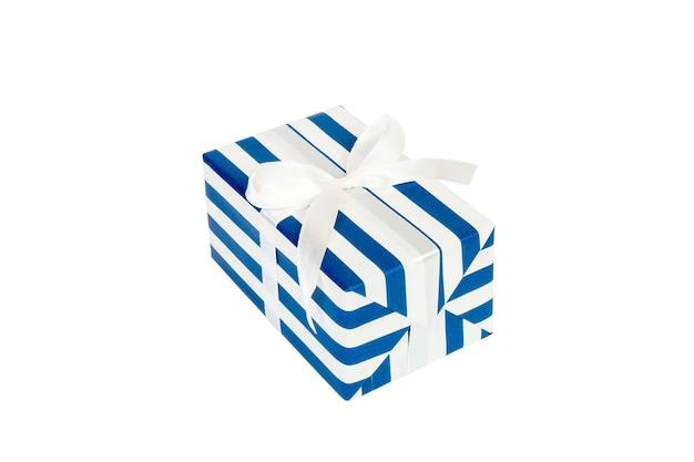 白いリボンが付いている青い紙のクリスマスまたは他の休日の手作りのプレゼント。白い背景、上面図に分離。感謝祭のギフトボックスのコンセプト。
