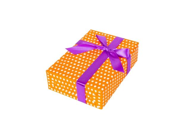 보라색 리본이 달린 주황색 종이에 크리스마스 또는 기타 휴일 수제 선물. 흰색 배경, 상위 뷰를 격리합니다. 추수 감사절 선물 상자 개념입니다.