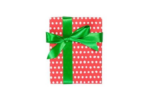 크리스마스 또는 다른 휴일 수제 선물은 녹색 리본이 달린 빨간 종이에 있습니다. 흰색 배경, 상위 뷰를 격리합니다. 추수 감사절 선물 상자 개념입니다.