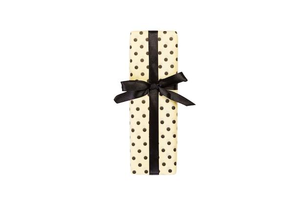 검은 리본이 달린 노란 종이에 크리스마스 또는 다른 휴일 수제 선물
