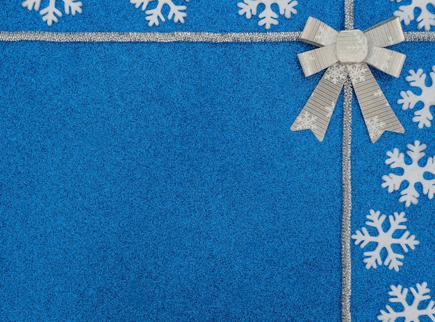 하얀 눈송이, 은색 반짝이와 활 크리스마스 또는 겨울 파란색 배경. 복사 공간이있는 평면 위치 스타일.