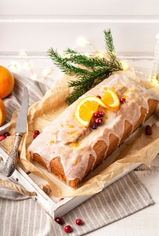 Christmas orange cake with cranberries and sugar icing on rustic wooden background