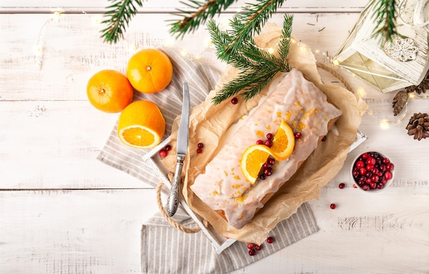 Christmas orange cake with cranberries and sugar icing on white rustic wooden background