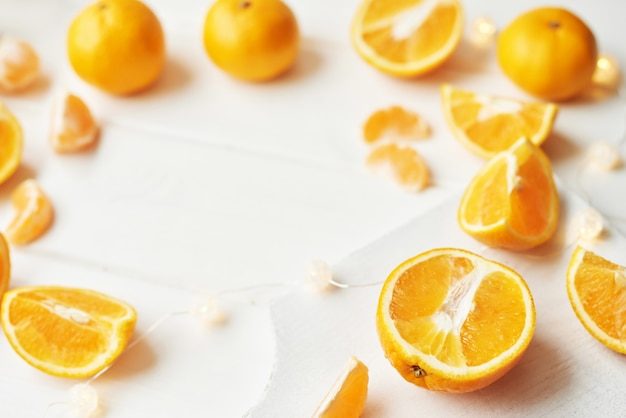 Christmas oranges and tangerines on a white by the window