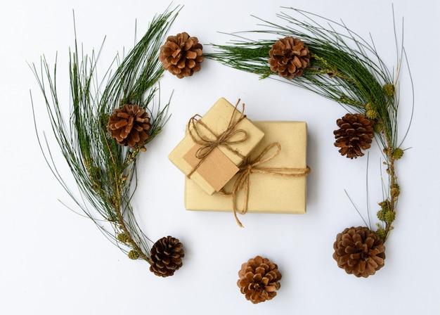 クリスマスornamateブラウンギフトボックスと松ぼっくりフラットホワイトバックグラウンドに新鮮な緑の枝を置く