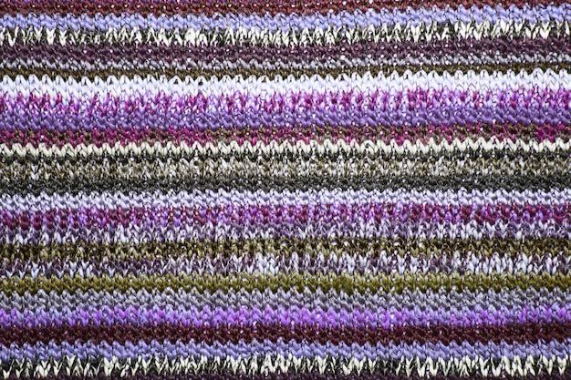 ストリップでクリスマスの装飾的な編み物。ニットセーターの背景のテクスチャ。本物のニット生地の織り目加工の背景。カラフルなセーターの質感