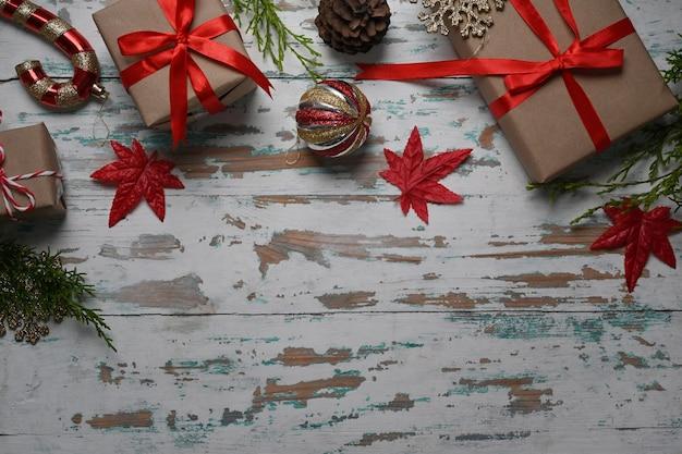 木製の背景にクリスマスの装飾品やギフトボックス。