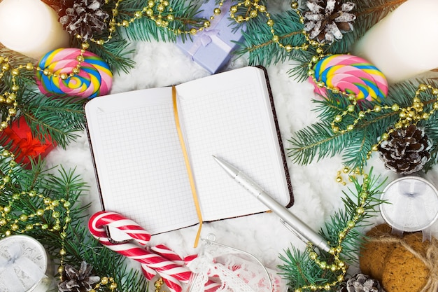 Christmas ornaments, fir branches and notebook with pen