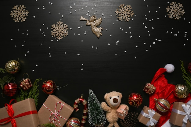 Christmas ornaments, gifts boxes  and fir tree branches on black background.