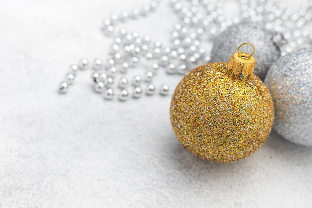 Christmas ornaments of gold and silver ball on blurred textured background with space for text, new year