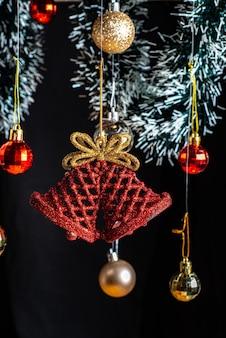 Рождественские украшения, выделенные дедом морозом, и рождественский колокольчик между красными и золотыми шарами.