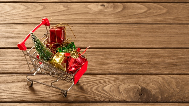 Christmas ornaments on miniature shopping cart over the wood for web banner