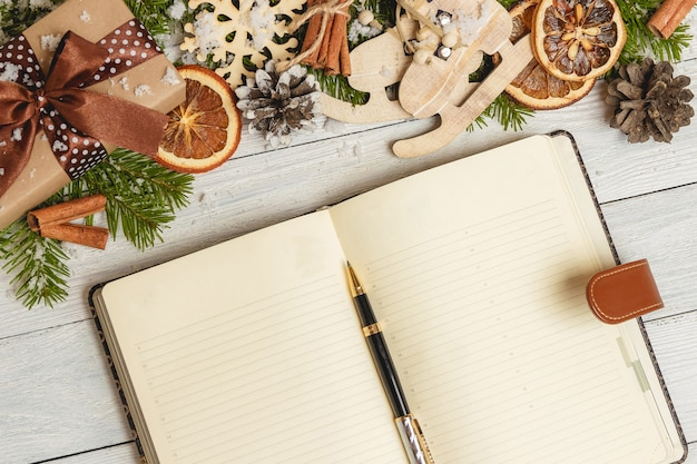 Christmas ornaments and an open blank notebook on a light wooden table
