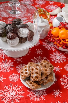 Christmas ornaments on table with citrus and rosehip cookies on festive table