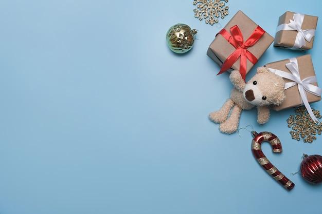 파란색 배경에 크리스마스 장식품, 테디 베어, 선물 상자.