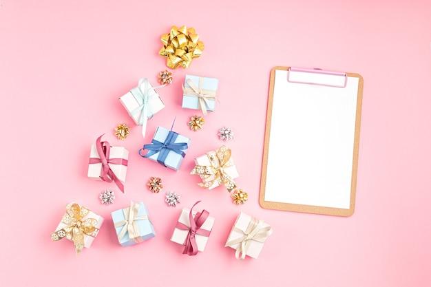 ピンクの表面にクリスマスツリーとクリップボードの形で配置されたクリスマスornametsとギフトボックス