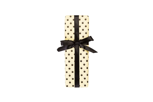 Christmas or other holiday handmade present in yellow paper with black ribbon