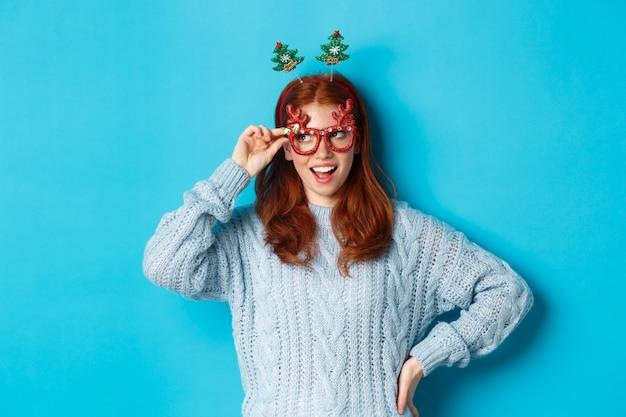 크리스마스 파티와 축 하 개념입니다. 새해를 축하하는 귀여운 빨간 머리 10대 소녀, 크리스마스 트리 머리띠와 재미있는 안경을 쓰고 왼쪽 즐겁게 보이는 파란색 배경