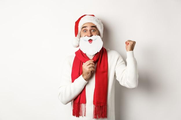 クリスマスパーティーとお祝いのコンセプト。新年を楽しんで、白ひげマスクでサンタの帽子で面白く見えて、拳ポンプを作って、喜んで興奮している若い男
